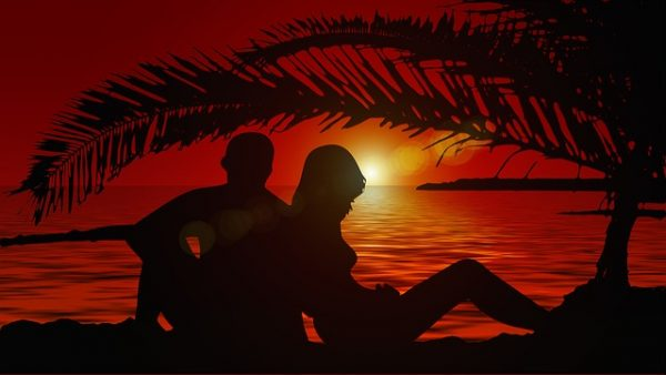 lovers-back-to-back-on-beach-at-sunset
